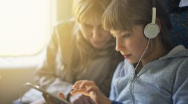 Smiling little girl aged 9 travelling on train with mother. They are playing with tablet. The girl is wearing white headphones.